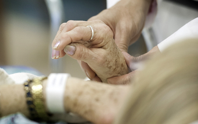 close-up of physician examining a female patient's hand